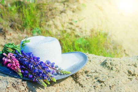 Hat near a bouquet of lupine flowers. Concept summer picnics. hat decorated with bouquet flowers. hat with lupins. rustic style home decor Banco de Imagens
