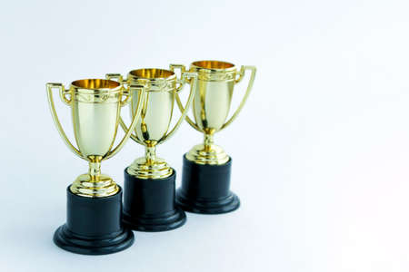 Three golden winner cups on a white background. Competitions concept. Banco de Imagens