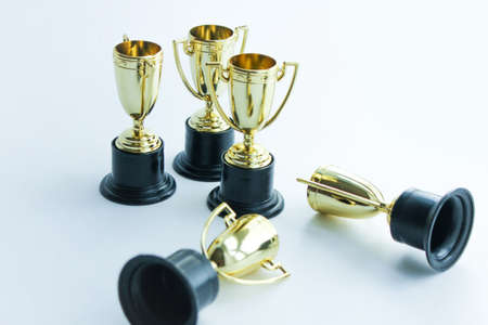 golden winner cups on a white background. Competitions concept. Banco de Imagens