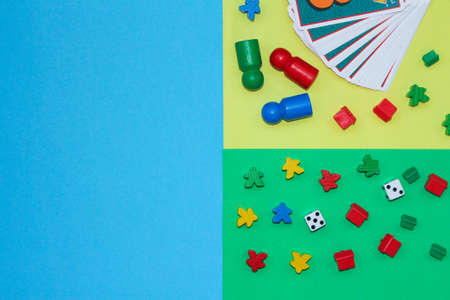 Board games on a multi-colored background: playing cards, cubes, figures. joint leisure with family or friends