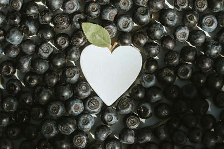 background of fresh blueberries with a white heart in the middle. berry harvest, vitamins Banco de Imagens