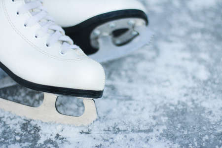 close-up of figure skates on an ice background. Ice skating outdoor activities with the family in winter