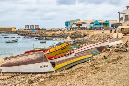 Sal Rei, Boa Vista, Cape Verde, Africa - February 8, 2018: Colorful boats at the fishing port, in the background the fish market and cargo area
