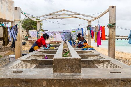 Sal Rei, Boa Vista, Cape Verde, Africa - February 8, 2018: Two women wash laundry by hand on a stone pool, clotheslines in the background