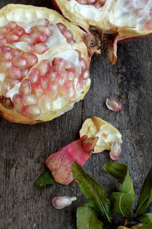 planking: Halves of a pomegranate with seeds and leaves on a wooden planking Stock Photo