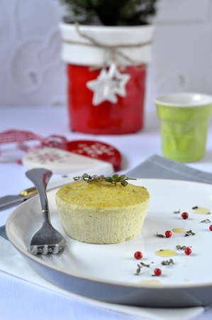 Small salt flan with ricotta, green peas and thyme, decoration  Christmas symbols, white tablecloth, cutlery   photo