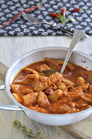 Tripe soup with tomatoes, spicy chili, basil, oregano in a metal pan  Italian food, South Italy  版權商用圖片