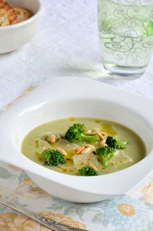 Cream soup with broccoli, beans, Parmesan cheese and pine nuts photo