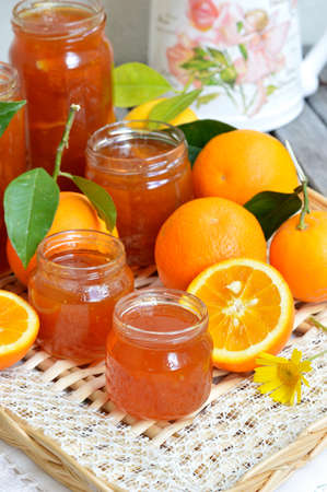 Several jars of orange marmalade homemade, fresh whole oranges with green leaves and oranges, cut in half  photo