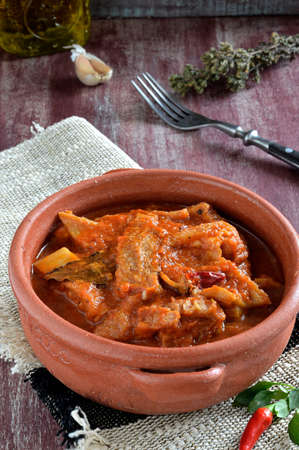 Tripe soup with tomatoes, spicy chili, basil, oregano in in a ceramic bowl  Italian food, South Italy  Close-up  photo
