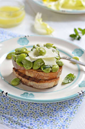 Toasted bread topped  bruschetta  with broad beans, Pecorino cheese and mint and on a light plate  Italian food  photo