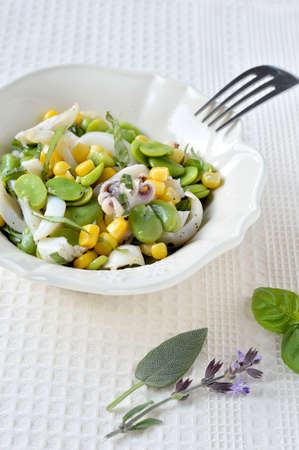 bens: Cuttlefish salad with fresh fava beans and corn with fresh aromatic herbs in a salad bowl