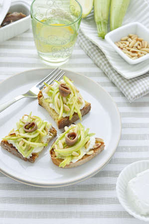 gastronome: Bruschetta  Toasted bread  with goat cheese, zucchini, salted anchovies and pine nuts on a table with a tablecloth striped texture  Stock Photo