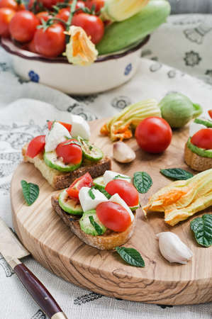 gastronome: Toasted bread topped (Bruschetta) with grilled zucchini, mozzarella, cherry tomatoes and fresh mint on a wooden cutting board, accompanied by whole cherry tomatoes, zucchini, zucchini flowers.