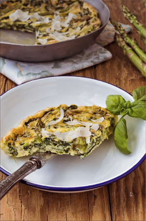 Italian omelette omelet slices on a white enamel plate with a knife accompanied by a frying pan with cooked omelette and fresh asparagus photo