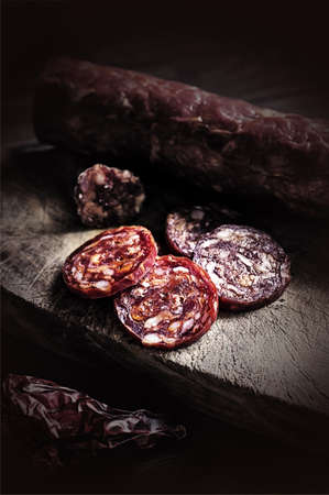 italian salami: Spicy Italian salami sliced over rustic wooden cutting board