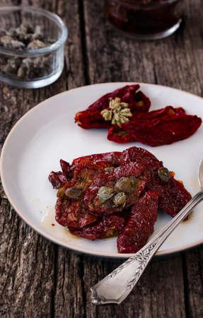 dried vegetables: Deliciosa Tomates secados al sol con alcaparras y or�gano en un frasco de vidrio. Verduras tradicionales de la comida italiana. Foto de archivo