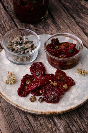 sun dried: Delicious Sun Dried Tomatoes with Capers and Oregano in a glass jar. Traditional Italian food vegetables. Stock Photo