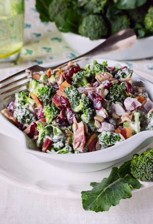 broccoli salad: Broccoli Salad with Bacon, Dried Cranberries, Sunflower Seeds Mayonnaise and Salad Bowl in white, close-up