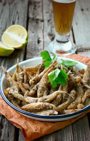 Fried fish and beer. Crispy roasted small fish. Italian Food. Shortnose greeneye Fried fish on a plate on a wooden background with a glass of beer. Small fish recipes. Retro Style.