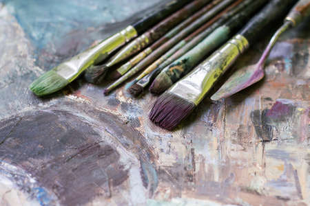 Old oil paint brushes on a painted canvas