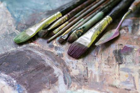 Viejos cepillos de pintura al óleo sobre un lienzo pintado