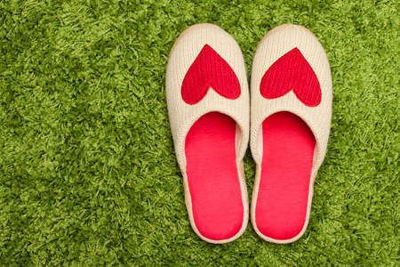 green carpet: Slippers with hearts on the green carpet Stock Photo