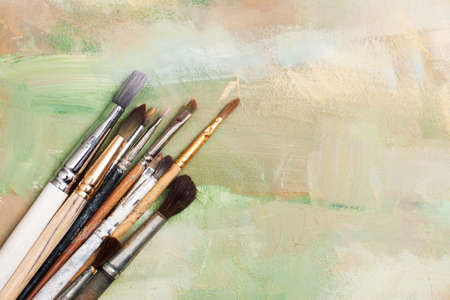old oil brush lying on a painted canvas expressive base or