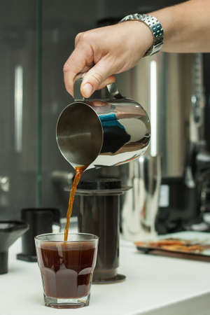 invigorating: Barista pouring fresh coffee in a transparent glass. Coffee prepared in AeroPress. Subject of professional preparation of coffee, baristas secrets, invigorating fresh coffee, etc.