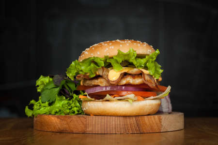 A delicious burger with bacon with lettuce on a wooden board on a dark background.  Photo causing appetite. The concept of fast food, but delicious food unwholesome.