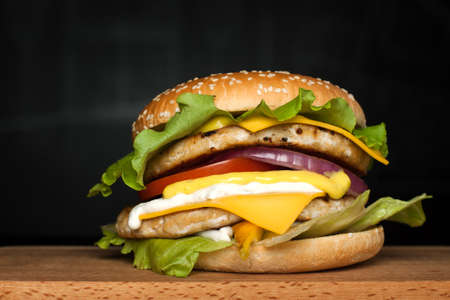 A delicious huge burger with two cutlets on a wooden board on a dark background.  Photo causing appetite. The concept of fast food, delicious food but unwholesome. Stock Photo