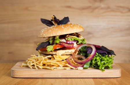 A delicious burger with two cutlets, basil, thin fries, lettuce and onion rings on a wooden board. Photo causing appetite. The concept of fast food, delicious but unwholesome food.