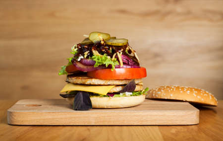 be careful: A delicious burger with removed top. Fresh bun, two juicy cutlets, lettuce, onion rings, tomato, pickles, cheese, potato straws and bright sauces. Photo appetizing, be careful. Stock Photo