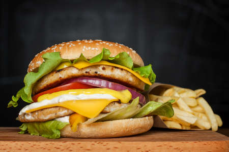 A delicious huge burger with two cutlets and French fries on a wooden board on a dark background.  Photo causing appetite. The concept of fast food, delicious food but unwholesome.
