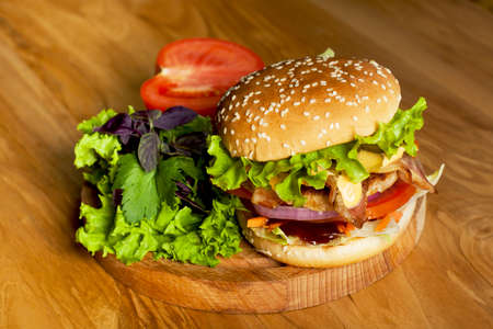 A delicious burger with bacon with lettuce, basil and tomato on a wooden background.  Photo causing appetite. The concept of fast food,delicious and unwholesome food.