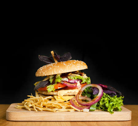 A delicious burger with two cutlets, basil, thin fries, lettuce and onion rings on a wooden board on the dark background. Photo causing appetite. The concept of fast food, delicious but unwholesome food.