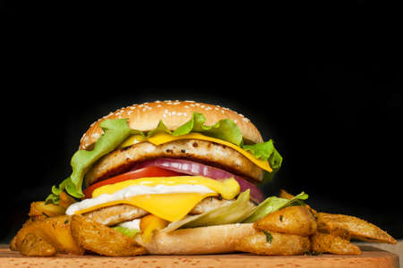 A delicious huge burger with two cutlets and fried potatoes on a wooden board on a dark background.  Photo causing appetite. The concept of fast food, delicious but unwholesome food. Stock Photo