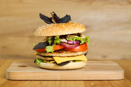 A delicious burger with two cutlets, basil on a wooden board. Photo causing appetite. The concept of fast food, delicious but unwholesome food. Stock Photo