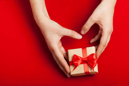 st: Hands holding gift in kraft box on a red background. The concept of St. Valentines day, weddings, engagements, Mothers Day, birthday, New Year, Christmas, holidays. Flat fly. Place for text