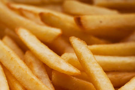 French fries close up. Saturated golden-yellow color. It can be used as background. The concept of fast food, delicious food, restaurants, cafes, etc. Banco de Imagens - 82523815