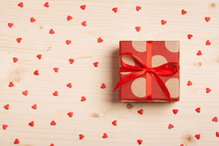 A gift on a wooden background with hearts. Surprise your loved one. The concept of the day of St. Valentines, weddings, engagements, Mothers Day, birthday, New Year, Christmas, holidays. Flat fly Stock Photo