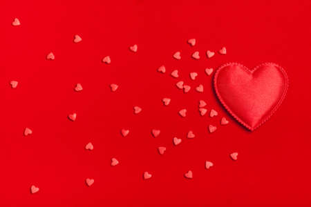 Many small hearts aspire on a red background. Concept of love, St. Valentines Day, lovers. Flat fly