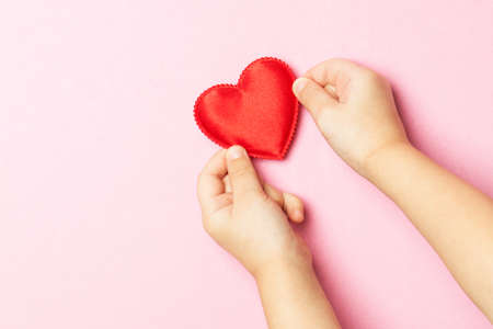 Children's hands holding the heart on a pink background. Concept of love, care, faith, hope, purity. Place for text. Flat fly