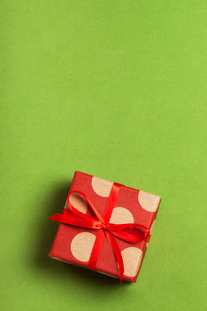 A gift on a greenery background. Surprise your loved one. The concept of the day of St. Valentines, weddings, engagements, Mothers Day, birthday, New Year, Christmas and other holidays. Flat fly Stock Photo