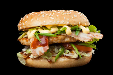 A delicious burger with bacon isolated on a dark background.  Photo causing appetite. The concept of fast food, delicious but unwholesome food. Photos can be used to create a menu or advertisement