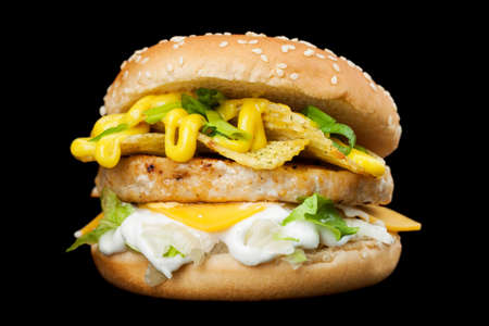A delicious burger isolated on a dark background.  Photo causing appetite. The concept of fast food, delicious but unwholesome food. Photos can be used to create a menu or advertisement Stock Photo