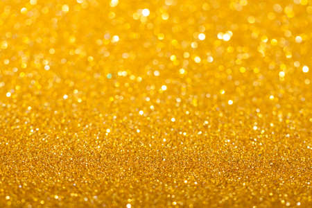 Golden festive background with sparkles in the bokeh. The concept of the celebration, the day of St. Valentine, New Year, birthdays, ceremonies, events, etc.