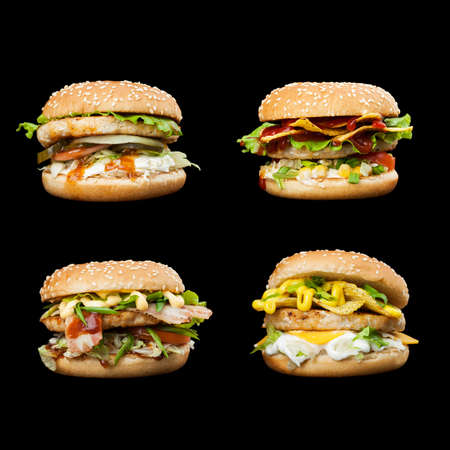 Set of four delicious burgers isolated on a dark background.  Photo causing appetite. The concept of fast food, delicious but unwholesome food. Photos can be used to create a menu or advertisement