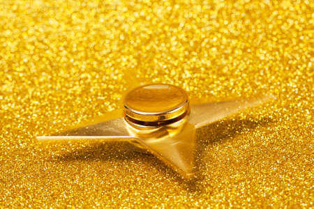 Gold spinner in the form of a star on a sparkling gold background. Spinner moves. The concept of the spinners trend, wealth, success, luxury