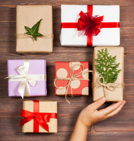 The girl's hand holds gifts packed in a minimalistic style on a wooden background. The concept of stylish, minimalistic holidays, hipsters, trends, New Year, Christmas, birthday, etc.